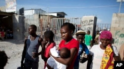 Milene Monime, 16, holding her two month old son Jefferson Thezan, stands along with other Haitian migrants just deported from Dominican Republic, at the border crossing in Malpasse, Haiti, June 17, 2015.
