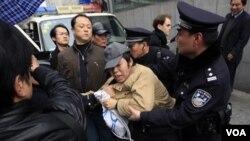 Polisi di Shanghai, Tiongkok, menahan seorang pria yang mengikuti aksi demonstrasi, Minggu (28/2).