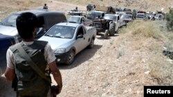 Anggota milisi Hezbollah mengawal konvoi pengungsi Suriah memasuki kota Arsal, Lebanon, 12 Juli lalu.