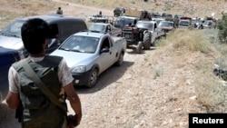 Des membres du Hezbollah escortent des réfugiés syriens à Arsal, Liban, le 12 juillet 2017.