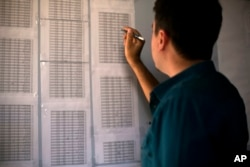 FILE - Bahzad Farhan Murad points to a list of missing and killed Yazidis in the small office where he collects evidence on Islamic State crimes against Yazidis, in Dohuk, Iraq, May 22, 2016.