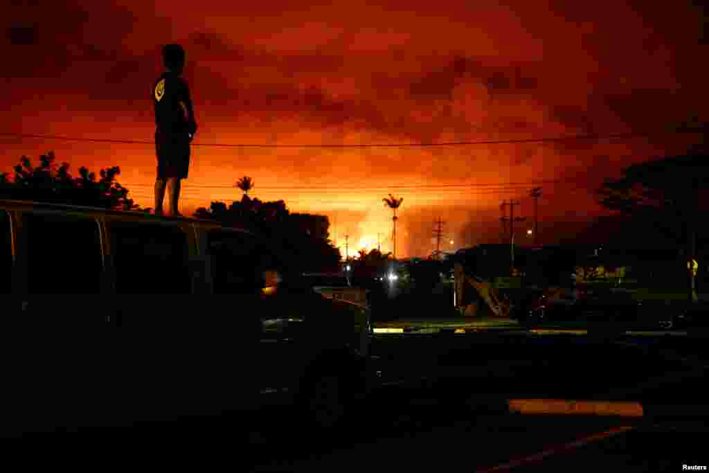 Darryl Sumiki, 52, of Hilo, watches as lava lights up the sky above Pahoa during ongoing eruptions of the Kilauea Volcano in Hawaii, June 2, 2018.