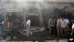 Warga setempat memeriksa lokasi sekitar meledaknya sepeda motor di dekat sebuah toko senjata di Kirkuk, 290 kilometer dari Baghdad, Irak (19/9).