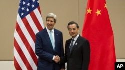 FILE - U.S. Secretary of State John Kerry, left, shakes hands with Chinese Foreign Minister Wang Yi as they pose for photos before their meeting at the 47th ASEAN Foreign Ministers' Meeting in Naypyitaw, Myanmar, Aug. 9,2014.