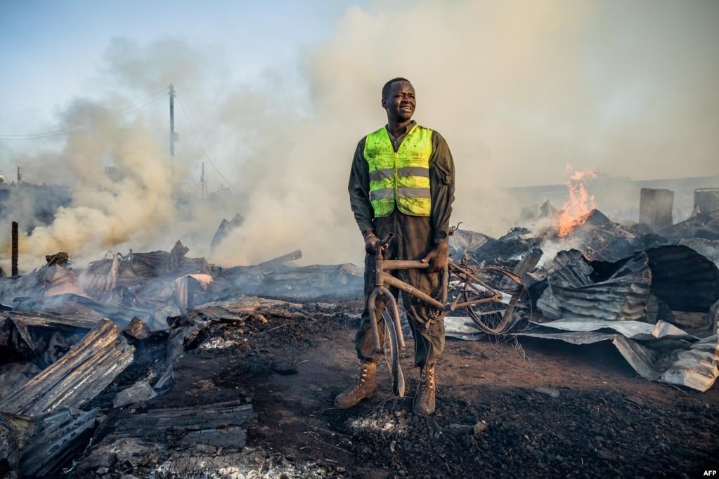 케냐 나이로비의 키베라 빈민가에서 화재가 발생한 가운데 구조를 돕는 주민이 불에 탄 자전거를 들고 서 있다.