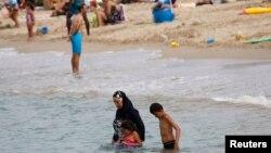 یک زن مسلمان در ساحل فرانسه با بورکینی یا حجاب اسلامی