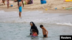 Une musulmane porte un burkini, un maillot de bain qui ne laisse que le visage, les mains et les pieds exposés, sur une plage à Marseille, France, 17 août 2016.