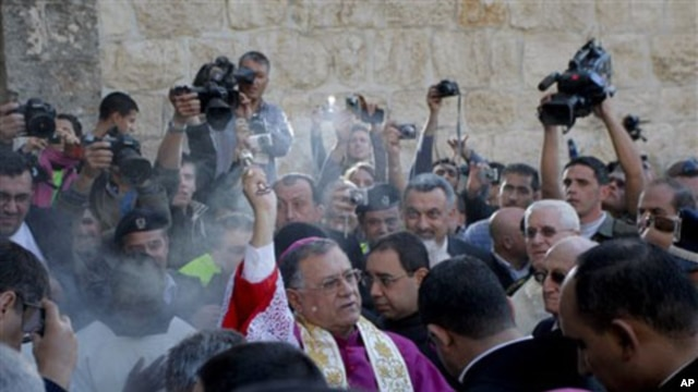 Latin Patriarch of Jerusalem Fouad Twal, center, performs a blessing before entering the Church of Nativity, traditionally believed by Christians to be the birthplace of Jesus Christ, before beginning Christmas celebrations in the West Bank town of Bethle