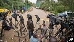 Local and foreign television crews line up behind a police cordon at the end of a street leading to the Westgate Mall in Nairobi, Kenya (AP Photo/Ben Curtis)