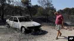 A man looks at a burned-out car during a wildfire near Kalyvia in Greece, Aug. 3, 2017.