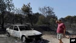 Seorang pria memperhatikan sisa mobil yang terbakar akibat kebakaran lahan dekat Kalyvia di Yunani, 3 Agustus, 2017.