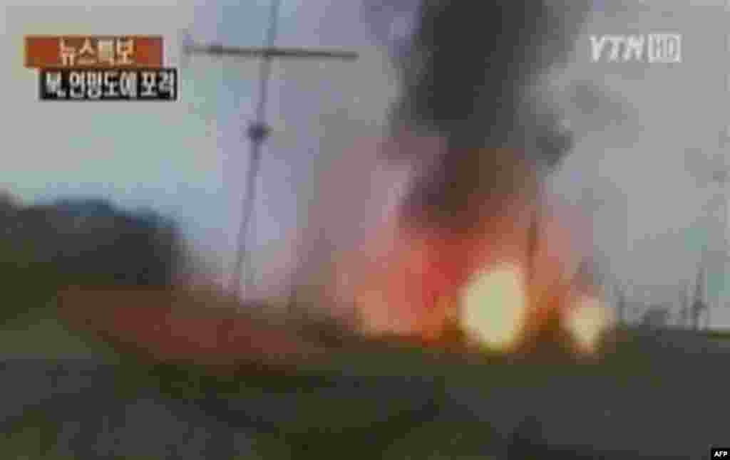In this image take from TV footage, smoke rises from South Korea's Yeonpyeong island near the border against North Korea, Tuesday, Nov. 23, 2010. North Korea shot dozens of rounds of artillery onto the populated South Korean island near their disputed wes