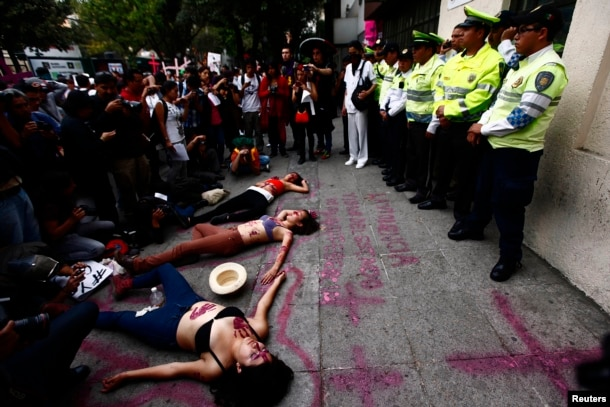FILE - Women lie on the ground during a performance in front of traffic police officers on the sidelines of a demonstration to demand justice for women who are the victims of violence, in Mexico City, March 8, 2013.
