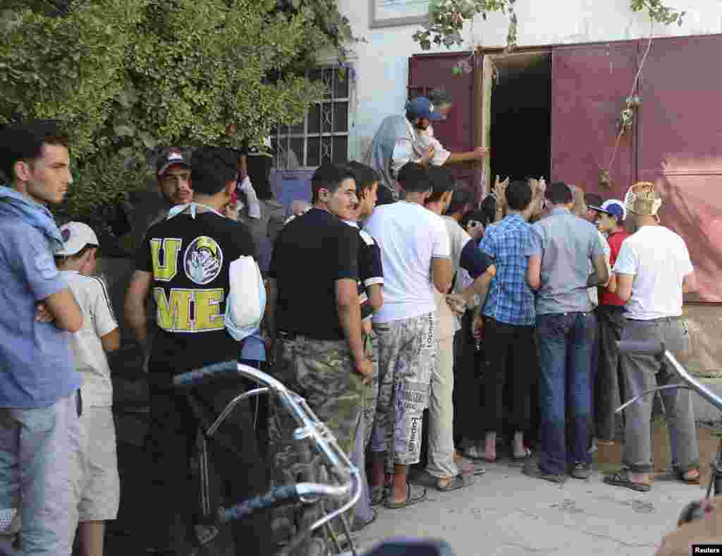 People stand in a line to receive water in Damascus, July 15, 2013.