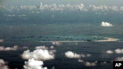 FILE - This aerial photo taken through a glass window of a military plane shows China's alleged on-going reclamation of Mischief Reef in the Spratly Islands in the South China Sea.