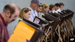 FILE - Voters use electronic voting machines at the Schiller Recreation Center polling station on election day, Nov. 3, 2015, in Columbus, Ohio.