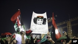 Women with a banner depicting Moammar Gadhafi celebrate the revolution against Gadhafi's regime and demand more women's rights in Tripoli, Libya, Sept. 2, 2011