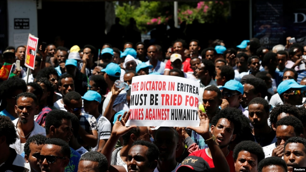 FILE - Eritrean refugees hold placards during a rally in support of a recent U.N. report that accused Eritrean leaders of committing crimes against humanity, outside the E.U. offices in Ramat Gan, Israel, June 21, 2016.