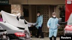 Para anggota staf medis bersiap membawa pasien dari Life Care Center, di mana ditemukan dua dari tiga kasus infeksi virus korona terkonfirmasi, di Kirkland, Washington, AS, 1 Maret 2020. (Foto: Reuters)