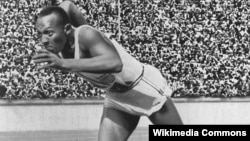 FILE - Jesse Owens is seen at start of a record-breaking 200-meter race during the Olympic Games in Berlin in 1936.