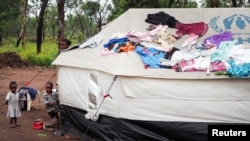 FILE - Children stand beside tents a refugee camp in Lovua, Angola, Sept. 13, 2017.