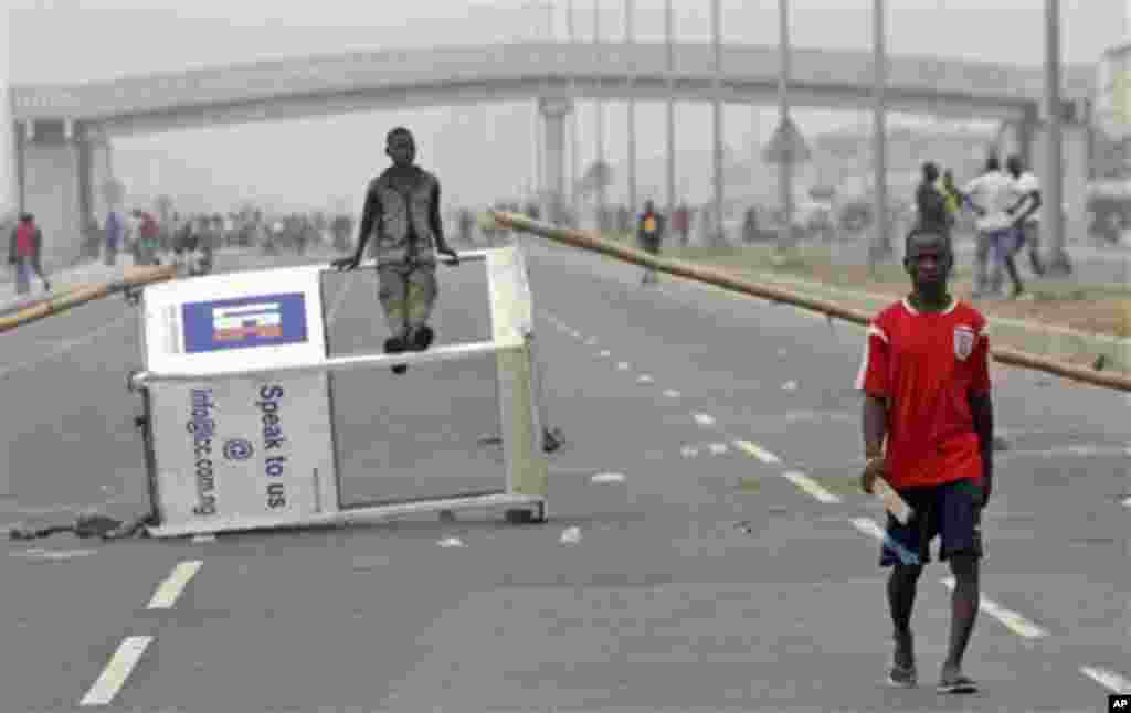 A protesters walk past a barricade at Lekki roads on the third day of nation wide strike following the removal of a fuel subsidy by the government in Lagos, Nigeria, Wednesday, Jan. 11, 2012. Nigeria's government is warning that a paralyzing national stri