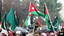 A Jordanian boy holds a national flag during a protest against Jordan's new Prime Minister Marouf Al Bakhit and in support of the Egyptian people in Amman, Jordan, February 4, 2011