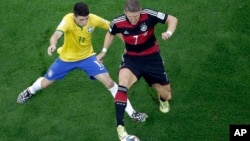 Brazil's Oscar (L) and Germany's Bastian Schweinsteiger vie for the ball during the World Cup semifinal soccer match between Brazil and Germany at Mineirao Stadium in Belo Horizonte, Brazil, July 8, 2014.
