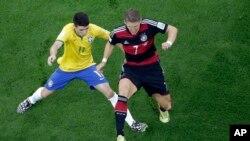 Oscar dari Brazil (kiri) dan Bastian Schweinsteiger (kanan) berebut bola dalam pertandingan semifinal, Selasa (7/8).
