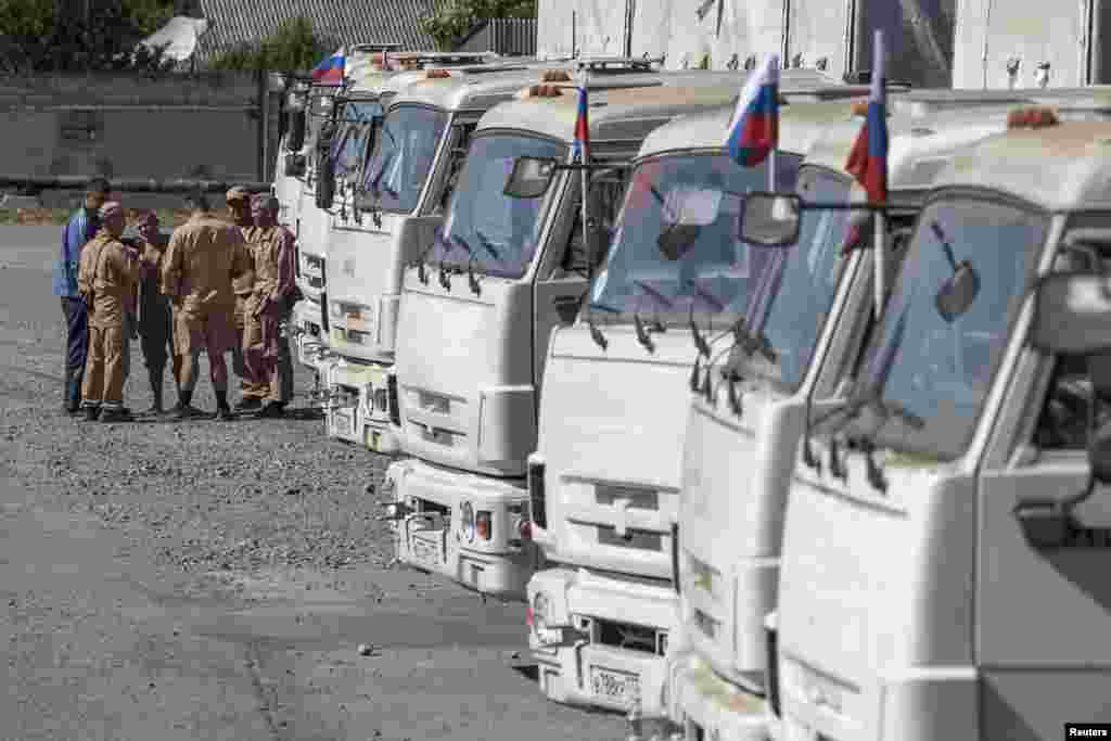 People stand near a Russian convoy of trucks carrying humanitarian aid in Donetsk, eastern Ukraine, Sept.0, 2014.