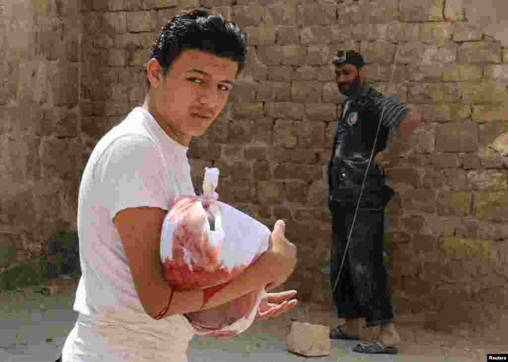 A man carries the body of a dead child after an airstrike in the rebel held Bab al-Nairab neighborhood of Aleppo, Syria.