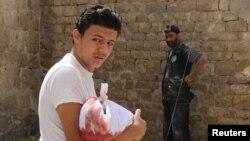 Seorang pria membawa jenazah bayi yang tewas akibat serangan udara di Bab al-Nairab, Aleppo, Suriah (25/8). (Reuters/Abdalrhman Ismail)
