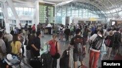 Para penumpang menunggu di Bandara Internasional Ngurah Rai, Bali (10/7).