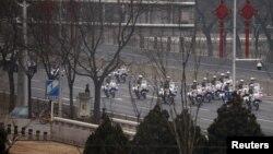 27일 중국 베이징을 가로지르는 창안 거리에서 공안 오토바이들이 북한 방문단이 탄 것으로 추정되는 차량행렬을 호위하고 있다.