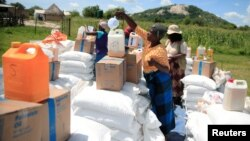 FILE:Villagers collect food aid distributed by the World Food Program (WFP) following a prolonged drought in rural Mudzi district, Zimbabwe, February 20, 2020. Picture taken February 20, 2020. REUTERS/Philimon Bulawayo