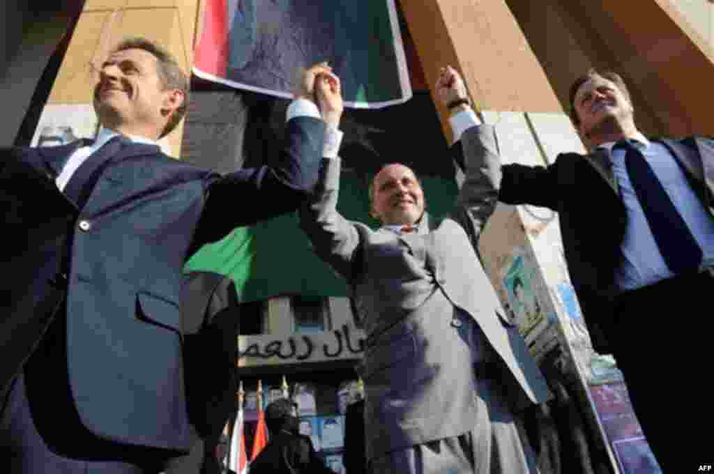 French President Nicholas Sarkozy, left, Libya's NTC leader Mustafa Abdul-Jalil, center, and British Prime Minister David Cameron, right, gesture during their visit to Benghazi, Libya, Thursday, Sept. 15, 2011. Cameron and Sarkozy gave Libya's new rulers