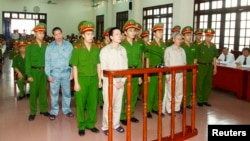 FILE - Doan Van Vuon, standing, fourth from left, and others stand with policemen in front of the dock at a court in Hai Phong, April 5, 2013, in this Vietnam News Agency photo.