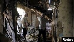 우크라이나 동부 도네츠크의 주거지역이 18일 밤 폭격을 받은 가운데 주민들이 파괴된 건물 안에서 잔해물을 정리하고 있다.