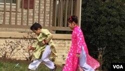 Hai em nhỏ trong trang phục áo dài Tết nô đùa trước sân nhà. (Hình: Trà Mi)