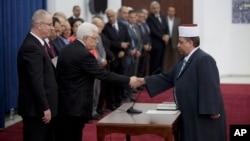 El presidente palestino Mahmoud Abbas saluda al nuevo ministro de asuntos religiosos, Youssef Daais, parte del nuevo gobierno de unidad palestino.