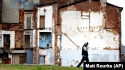 A man walks through a vacant lot where the impression on a demolished home remains on a standing building.