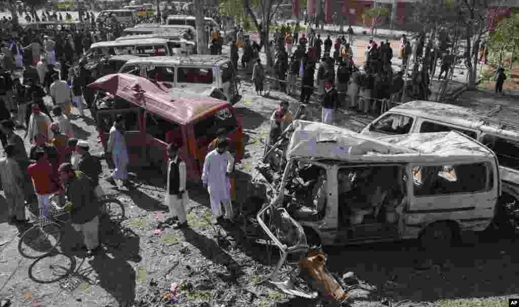 People visit the site of a bomb blast at a bus station in Peshawar, Pakistan, February 23, 2012. (AP Photo)