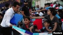 Ramazan'da kurulan iftar sofralarında dağıtılan yiyecek kutularından almak için çabalayan Suriyeli çocuklar