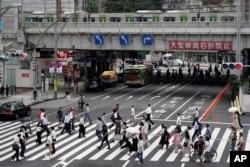 Para pejalan kaki berjalan melintasi penyeberangan jalan yang ramai di dekat Stasiun Ueno, Tokyo, Jumat, 30 Juli 2021. (AP)