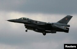 FILE - A Polish Air Force F-16 fighter jet flies near an airbase in Lask near Lodz, central Poland, June 28, 2013.