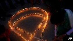 尼泊尔人11月30日在加德满都点燃蜡烛,形成红缎带的形状,支持艾滋病患者