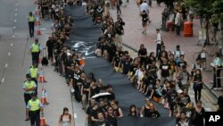 Những người phản đối cầm dải vải đen dài 500 mét tuần hành trên đường phố Hong Kong hôm Chủ nhật, để chứng tỏ họ quyết tâm muốn có phổ thông đầu phiếu thực sự, 14/9/14