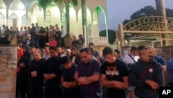 Worshippers pray for victims and families of the Christchurch shootings during an evening vigil a the Lakemba Mosque, March 125, 2029, in Wakemba, New South Wales, Australia.