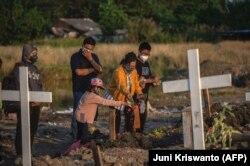 Anggota keluarga memberikan penghormatan terakhir saat pemakaman orang terkasih yang meninggal karena COVID-19 di sebuah pemakaman di Surabaya pada 9 Agustus 2021. (Foto: AFP/Juni Kriswanto)