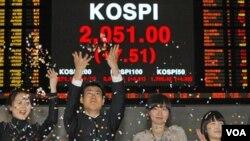 Para pegawai Bursa Saham Korea menyambut gembira kenaikan tertinggi indeks saham KOSPI pada penutupan pasar saham, 30 Desember 2010.